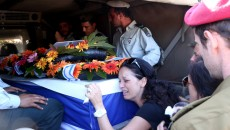 "Wife of IDF (Isreal Defense Force) reservist Yair Ashkenazi, seen crying on the coffin carrying her husband, at Ashkenazi's funeral, at the military cemetery in Rehovot on July 25, 2014. Ashkenazi, a combat soldier in a reserve brigade, was killed during combat in the northern Gaza Strip. Since the beginning of Operation ""Protective Edge"" more than 800 Palestinians and 34 Israeli soldiers have been killed. Israel launched its military offensive on July 08 with the declared objective of stopping Hamas firing rockets from Gaza. Photo by FLASH90"