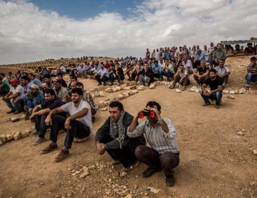 Kurds in Turkey look over the border towards Kobani. Credit: David Takaki / Twitter.