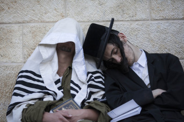 An ultra-Orthodox man falls asleep on an Israeli soldier at the Western Wall. Credit: Yonatan Sindel/Flash90.